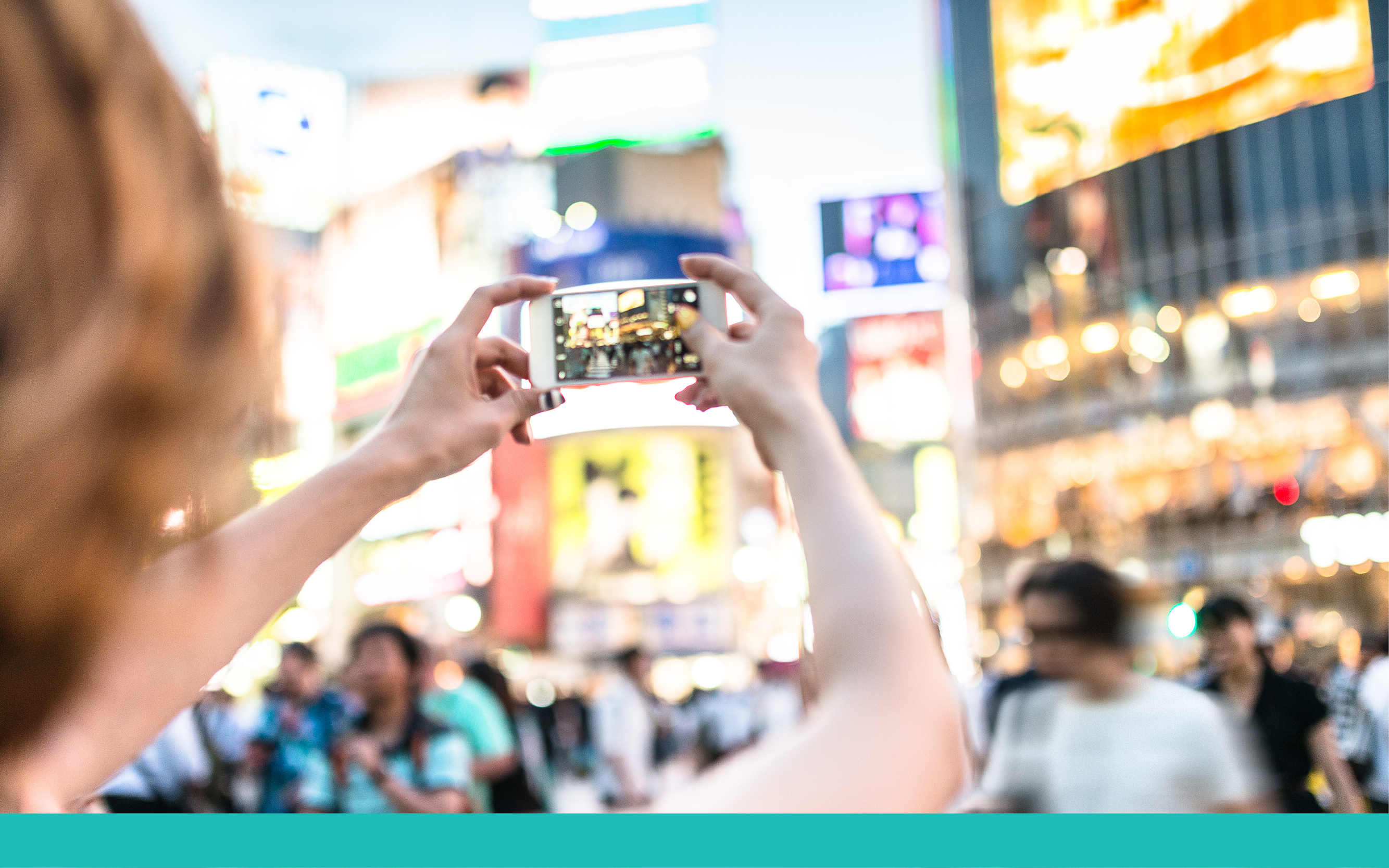 Woman holding phone in busy city street taking a picture